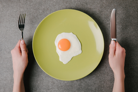 cropped shot of person holding fork and knife ready to eat tasty fried egg on plate