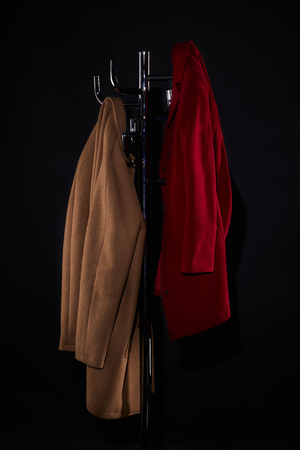 classic coats on coat rack isolated on black Foto de archivo - 106710223