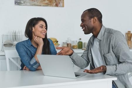 african american girlfriend and boyfriend using laptop in kitchen