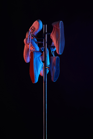various shoes hanging on coat rack under toned light isolated on black