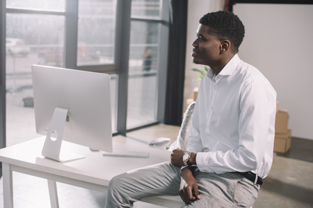 pensive young african american businessman sitting in table and looking away in new office