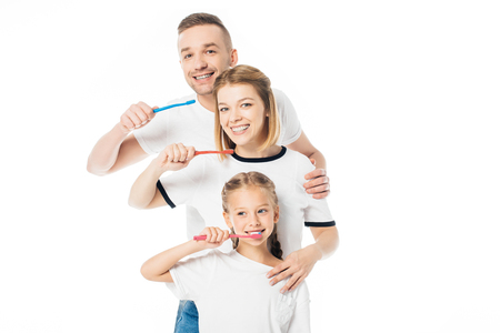 portrait of family in similar clothing with toothbrushes isolated on white