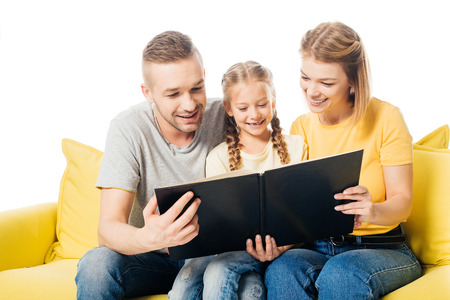 happy family looking at photos in photo album together while sitting on yellow sofa isolated on white Stock Photo