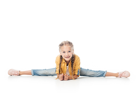 smiling little child stretching, doing split and looking at camera isolated on white