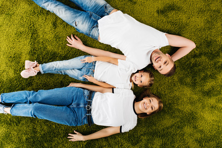 overhead view of happy family in similar clothing lying on green lawn 스톡 콘텐츠
