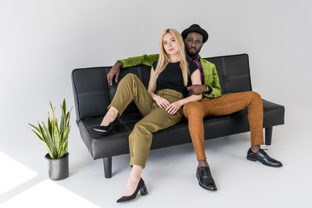 multicultural fashionable couple sitting on black sofa on grey background