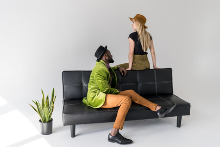 multicultural fashionable couple in hats on black sofa on grey backdrop