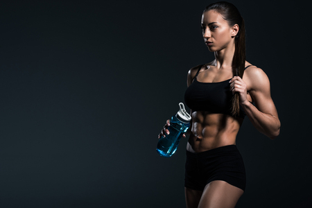 beautiful muscular sportswoman with water in sport bottle, isolated on grey Imagens