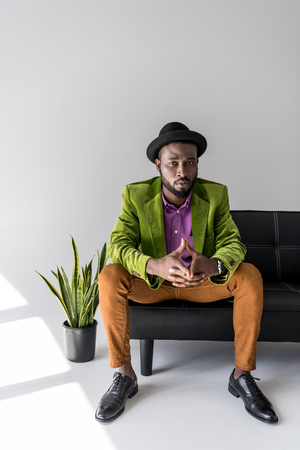 stylish african american in hat sitting on black sofa o grey background
