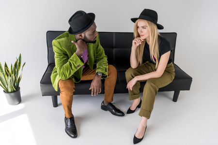 multicultural fashionable couple in hats looking at each other on black sofa on grey backdrop