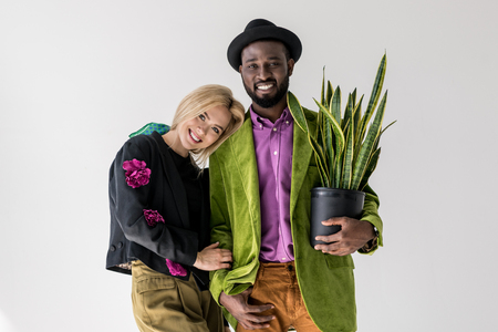 portrait of smiling interracial stylish couple with green plant in flowerpot posing isolated on grey Stock Photo