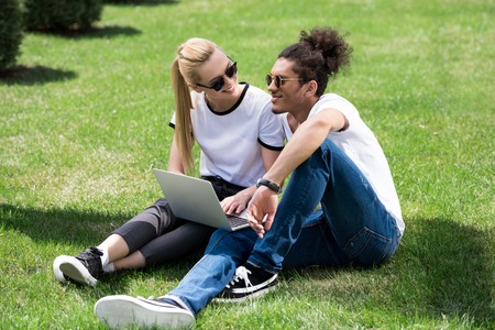 young multiethnic couple smiling each other while using laptop on grass Stok Fotoğraf