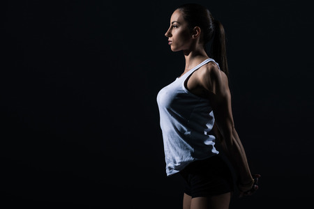 beautiful athletic sportswoman stretching arms, isolated on black