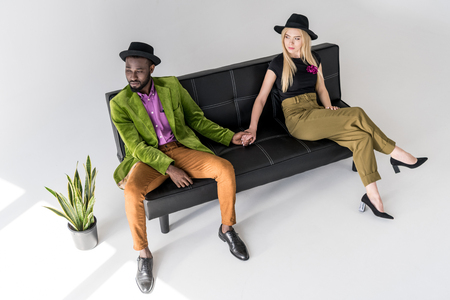 multicultural fashionable couple in hats holding hands on black sofa on grey backdrop Stock Photo