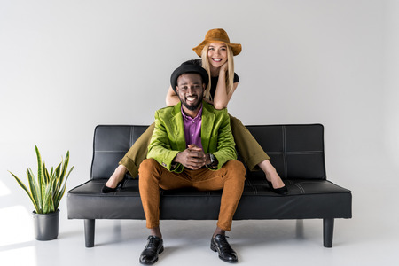cheerful multicultural fashionable couple in hats sitting on black sofa on grey background Stock Photo