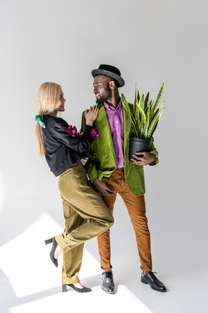 smiling interracial stylish couple with green plant in flowerpot posing on grey backdrop Stock Photo
