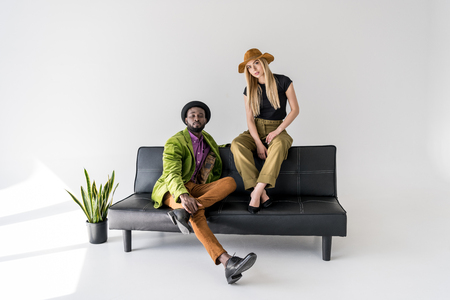 young multicultural fashionable couple sitting on black sofa on grey backdrop