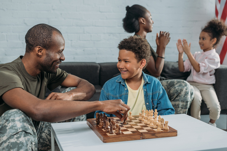 Smiling soldier playing chess with his son while mother and daughter playing together 스톡 콘텐츠