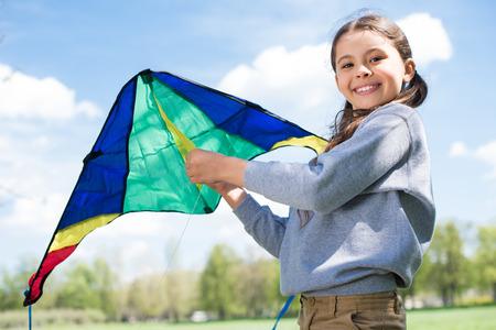 smiling little child holding kite in park
