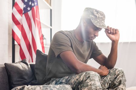 African american soldier in camouflage clothes sitting on sofa