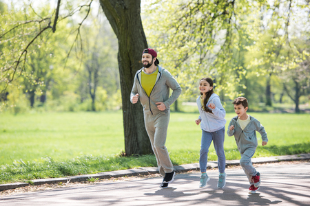 happy sportive family running on path in park 스톡 콘텐츠