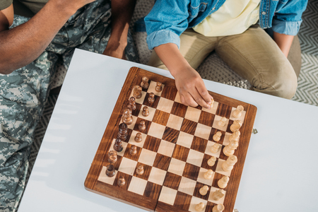 Close-up view of father and son playing chess game