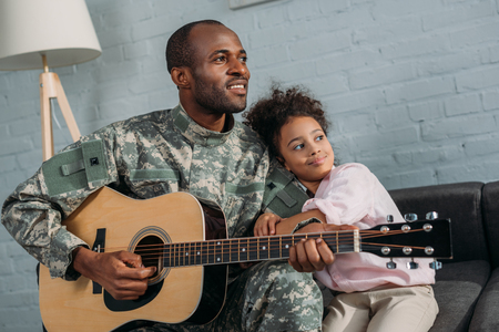 Father in army uniform playing guitar and hugging daughter Stock Photo - 106750215