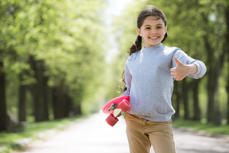 smiling child with skateboard doing thumb up gesture in park