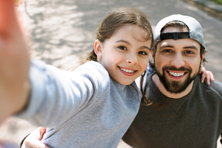 dochter nemen selfie lachende vader in park