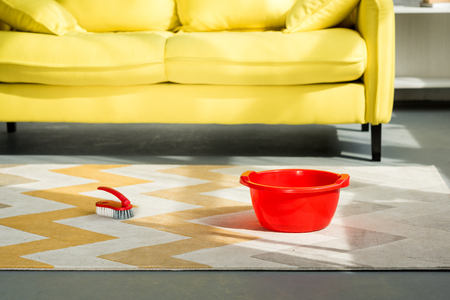 red bucket and cleaning brush on carpet on floor Stock Photo