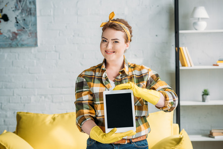 beautiful woman in cleaning gloves showing tablet at home Stock Photo