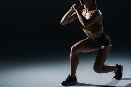 cropped view of sporty female bodybuilder doing lunges, on black Stock Photo