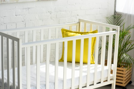 close up view of empty baby crib with yellow pillow in room