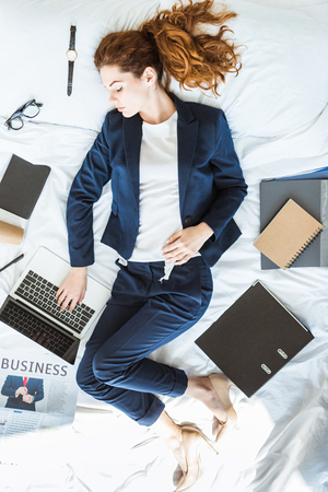 Top view of businesswoman in suit typing on laptop while lying in bed among folders and documents 版權商用圖片