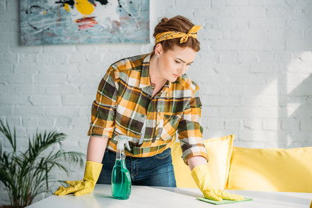 beautiful woman dusting table at home