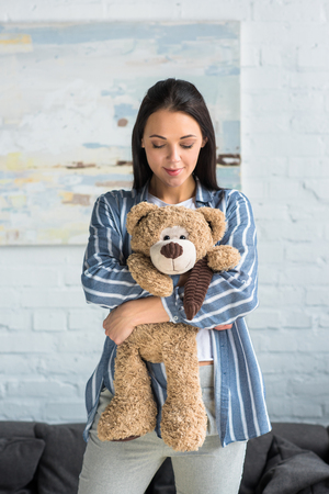 portrait of smiling attractive woman with teddy bear in hands at home