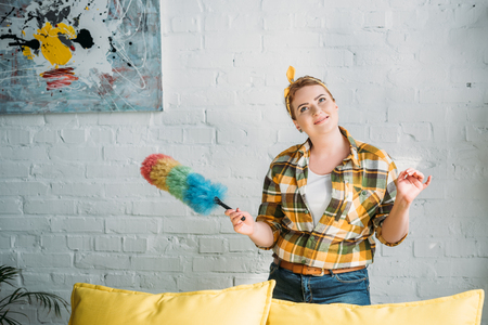 pensive beautiful woman posing with colored dust brush for cleaning at home