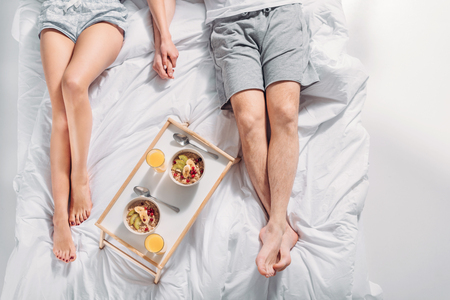 partial view of couple with breakfast on wooden tray resting on bed 版權商用圖片
