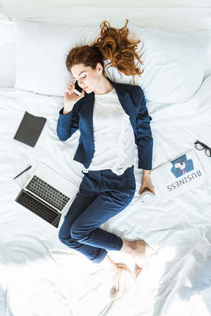 Top view of businesswoman in suit talking on phone in bed among folders and documents