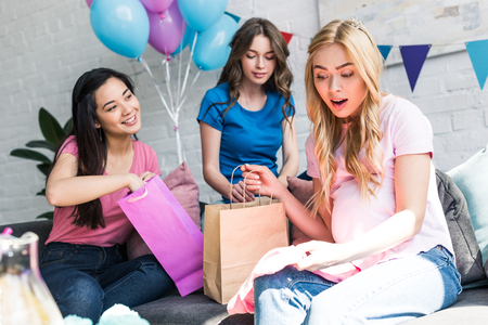 surprised pregnant woman looking at presents from multicultural friends on baby-party