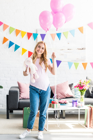 beautiful pregnant woman standing with bundle of balloons and rabbit toy at baby-party
