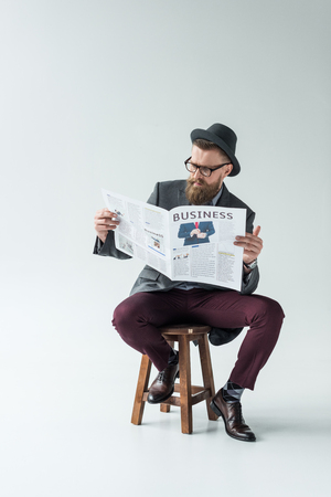 Stylish bearded businessman reading business newspaper while sitting on stool