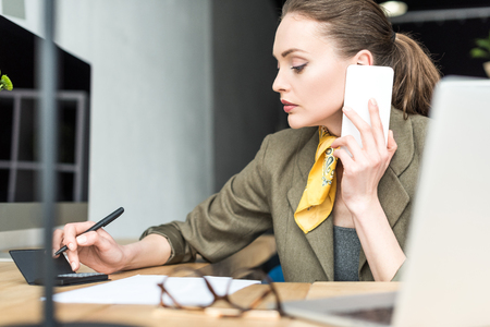 concentrated businesswoman using calculator and talking by smartphone in office Foto de archivo
