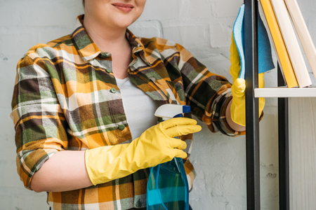 cropped image of woman dusting shelves at home Stock Photo