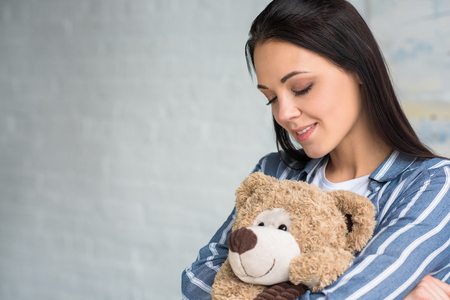 portrait of smiling attractive woman with teddy bear at home