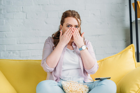 shocked beautiful woman watching movie with popcorn at home