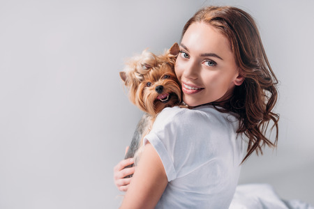 portrait of young smiling woman with yorkshire terrier looking at camera isolated on grey