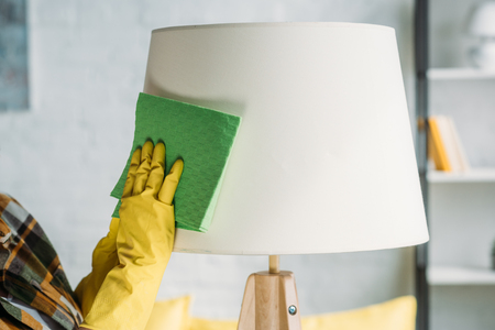 cropped image of woman dusting lamp with rag at home Stock Photo