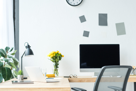 close up view of empty workplace with blank computer screen, laptop, eyeglasses and bouquet of chrysanthemum flowers in office Banco de Imagens