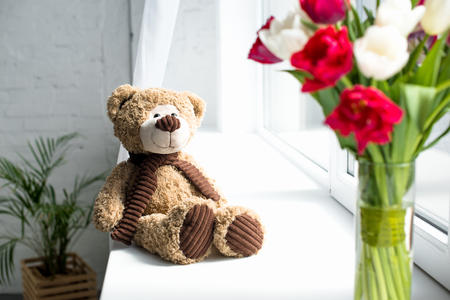 selective focus of teddy bear and bouquet of tulips in vase o window sill at home Imagens